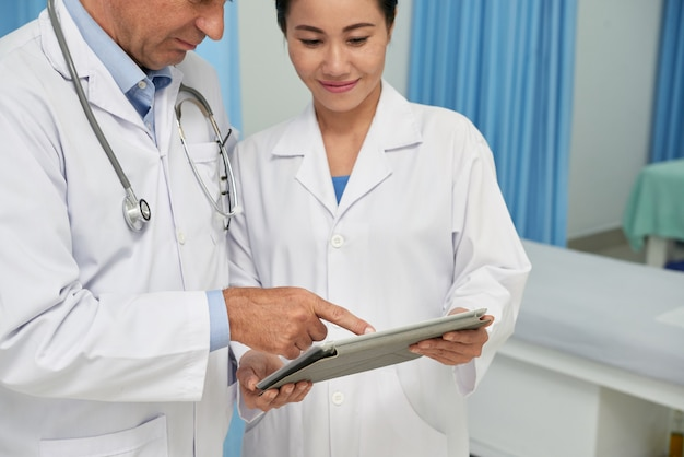 Medical workers with tablet computer Free Photo