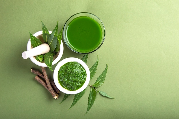 Medicinal neem leaves in mortar and pestle with neem paste, juice and twigs on green surface Premium Photo