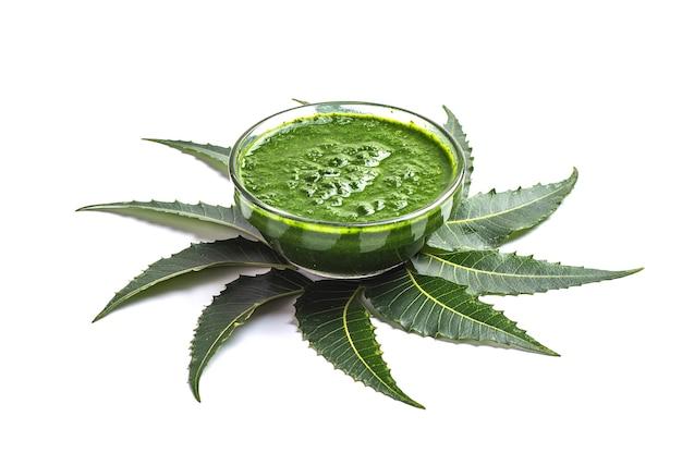 Лекарственные листья нима с пастой в миске на белой поверхности. Premium Фотографии