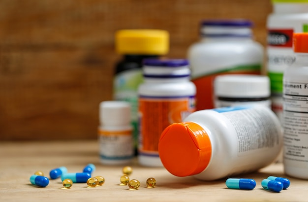 Medicine bottles and tablets on wooden desk Free Photo
