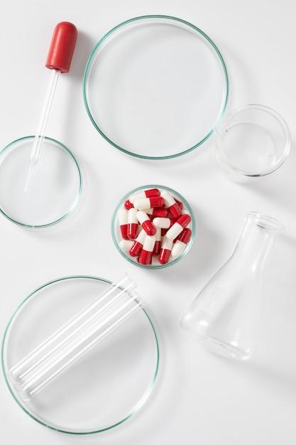 건강 치료를 위해 흰색 배경에 실험실 장비와 약 캡슐 프리미엄 사진