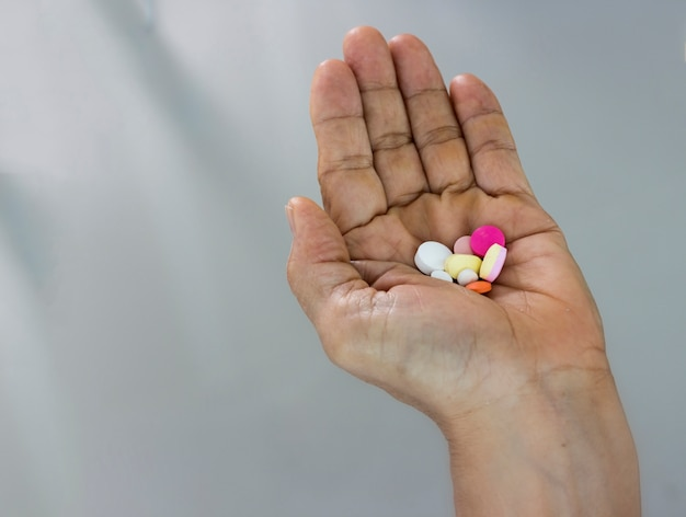 Medicine concept; pills in hand isolated on blurred grey Premium Photo