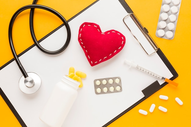 Medicine falling from bottle over clipboard; stethoscope; stitched heart shape; injection; blister packed medicine against yellow desk Free Photo