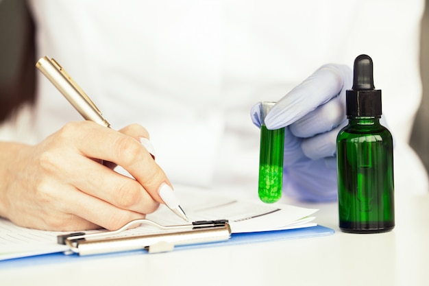 Medicine. lab technician doing chemistry experiment. close up of scientist checking test tube in laboratory Premium Photo