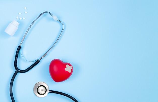 医学の聴診器、薬の瓶、心臓専門医のテーブルの石膏上面と赤いハート Premium写真