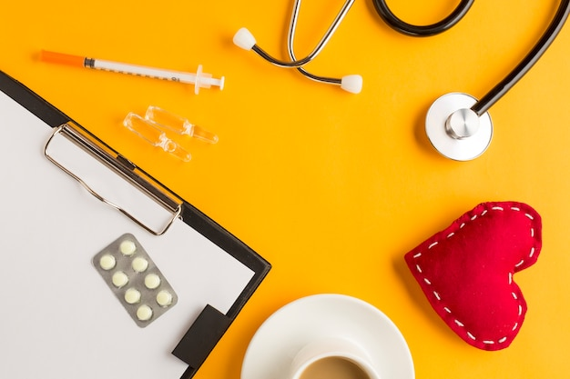 Medicines over clipboard with stitched heart; ampoule; stethoscope and coffee cup; injection on yellow background Free Photo