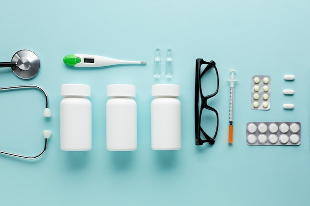 Medicines and healthcare accessories arranged on blue surface Free Photo