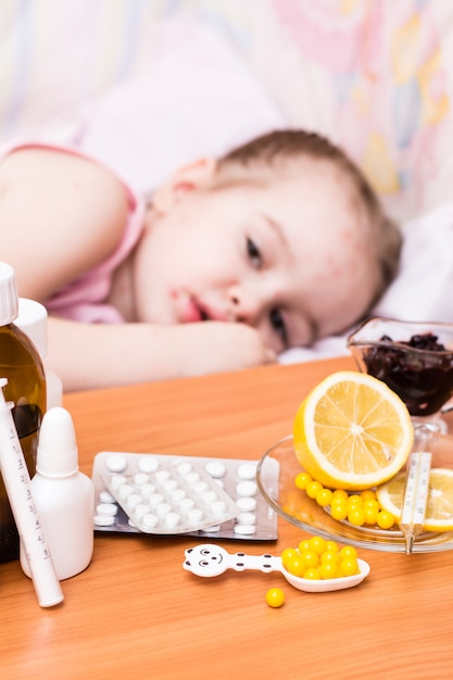 Medicines and vitamins on the table  child in a bed that has chickenpox Premium Photo