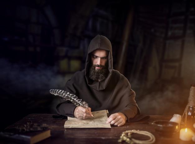 Средневековый монах в халате пишет гусиным пером   Премиум Фото