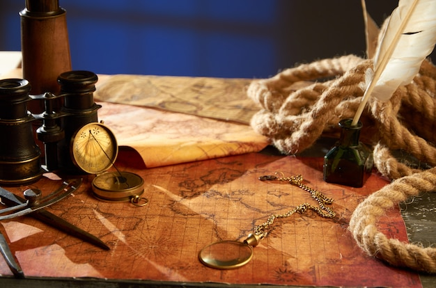 Medieval objects for navigation in the form of maps magnifying glass and compass Premium Photo