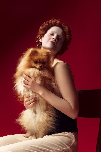 小さな子犬や犬と一緒に赤い壁の椅子に座っている黒いコルセットと寝間着の公爵夫人としての中世の赤毛の若い女性。時代、現代性、ルネッサンスの比較の概念。 無料写真