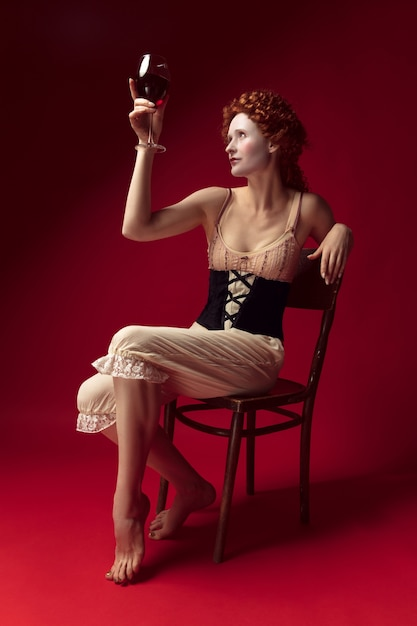 Medieval redhead young woman as a duchess in black corset and night clothes sitting on a chair on red space with a glass of wine Free Photo