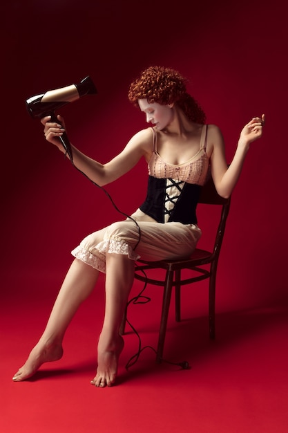 Medieval redhead young woman as a duchess in black corset and night clothes sitting on the chair on red wall. doing her hair with dryer. concept of comparison of eras, modernity and renaissance. Free Photo