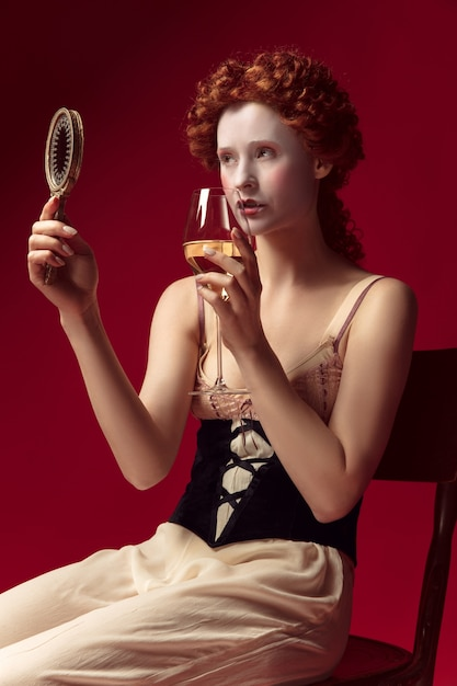 Medieval redhead young woman as a duchess in black corset and night clothes sitting on red space with a mirror and a glass of wine Free Photo