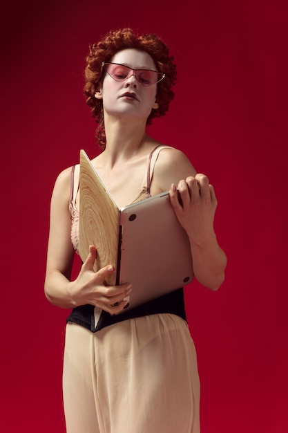 Medieval redhead young woman as a duchess in black corset, sunglasses and night clothes standing on red wall with a laptop as a book. concept of comparison of eras, modernity and renaissance. Free Photo