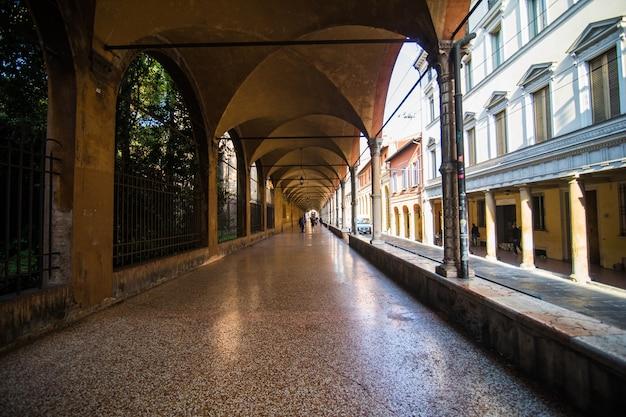 Средневековый уличный портик с яркими домами в старом городе в солнечный день, болонья, эмилия-романья, италия Бесплатные Фотографии