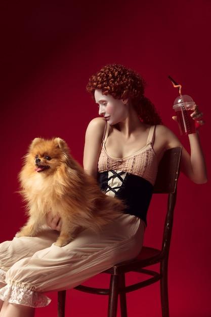 ジュースを飲み、小さな犬を保持している中世の若い女性 無料写真