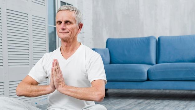 Meditating senior man with praying hands Free Photo