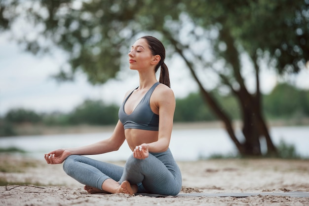 Meditating with sounds of nature. brunette with nice body shape in sportive clothes have fitness day on a beach Free Photo