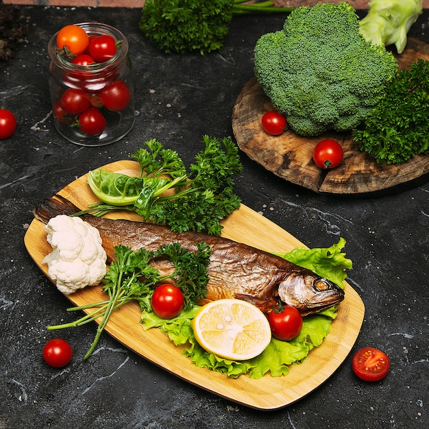 Mediterranean food, smoked herring fish served with green onion, lemon, cherry tomatoes, spices, bread and tahini sauce Free Photo