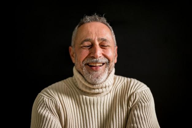 Medium close up shot old man laughing Free Photo
