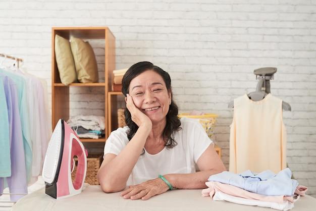 Medium closeup of asian senior wowan enjoying housework leaning on ironboard and smiling cheerfully Free Photo