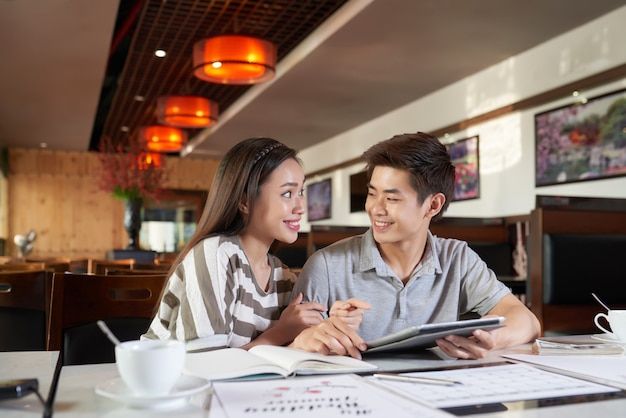 Medium closeup of young asian couple discussing upcoming trip to europe Free Photo