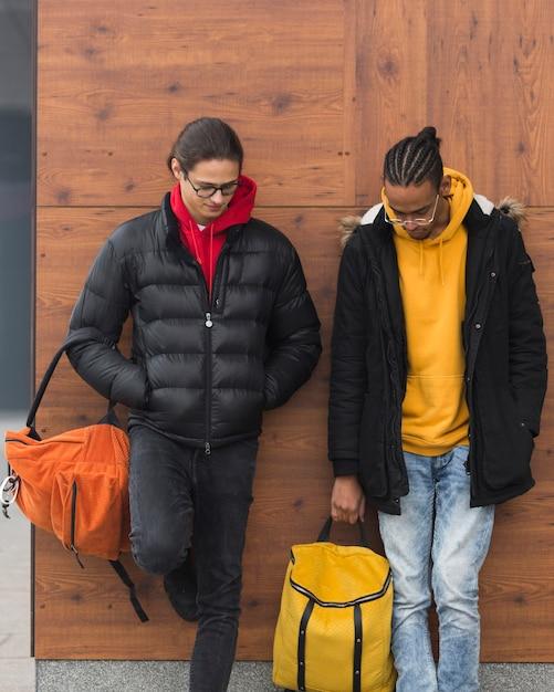Medium long shot guys standing with bags Free Photo