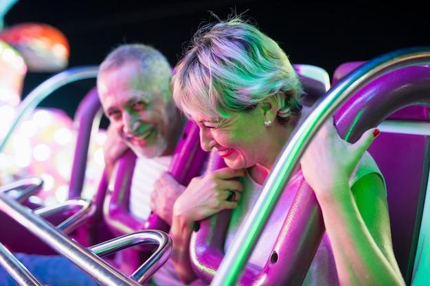 Medium shot adult couple in amusement ride Free Photo