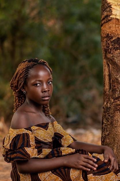 木の近くでポーズをとるミディアムショットアフリカの女の子 無料写真