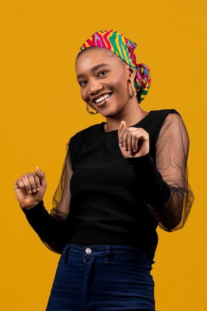 Среднего выстрела африканская женщина танцует в желтой студии Бесплатные Фотографии