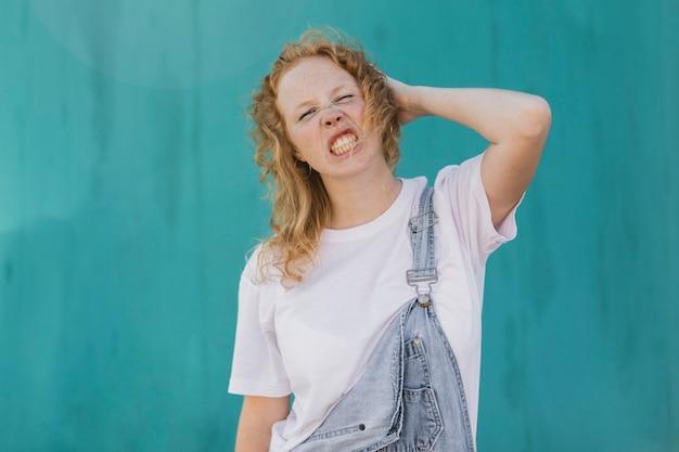 Medium shot angry girl with blue background Free Photo