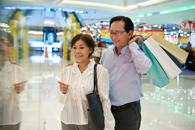 Medium shot of asian middle aged couple window shopping at a mall, man holding  shop bags Free Photo
