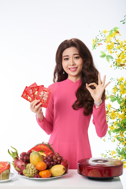 Medium shot of asian woman congratulating on spring festival with a gesture Free Photo