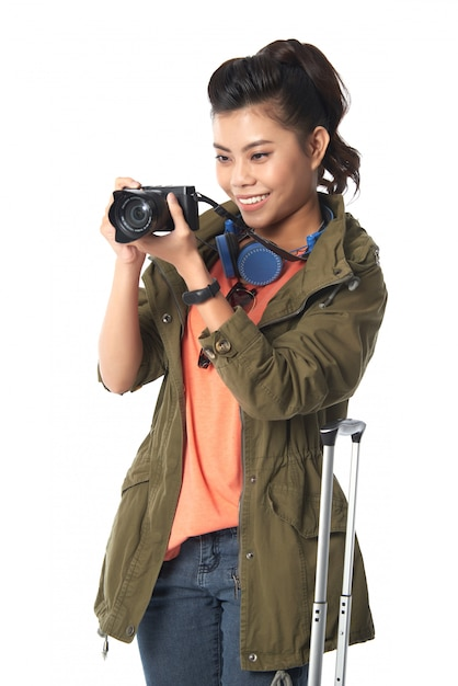 Medium shot of asian woman holding a photo camera taking picture Free Photo