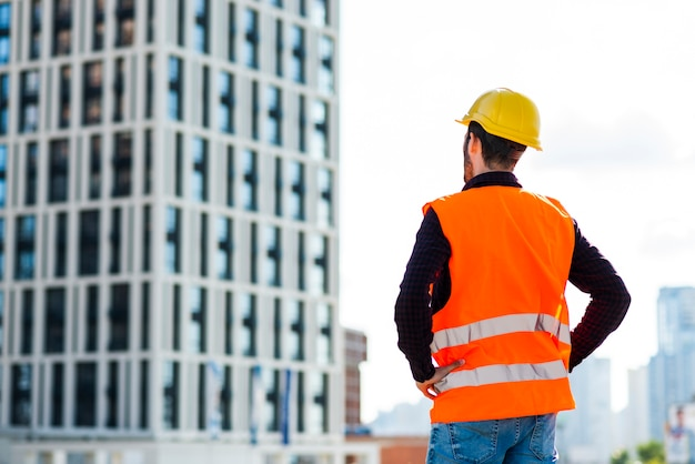 Medium shot back view of architect supervising construction Free Photo
