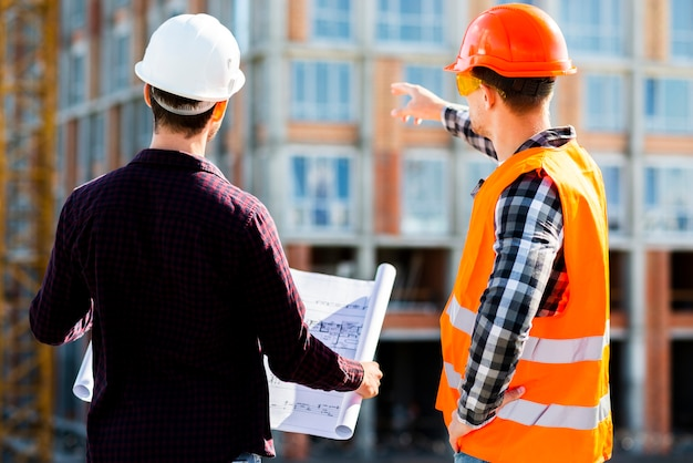 Medium shot back view of engineer and architect supervising construction Free Photo