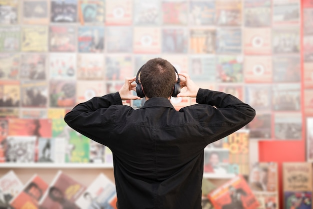 Medium shot back view of young man listening to music in store Free Photo