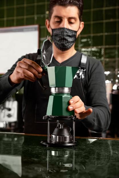 Бариста среднего размера с маской готовит кофе Бесплатные Фотографии