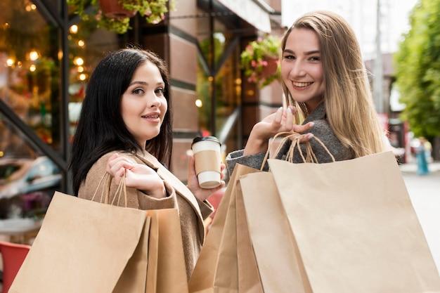 Migliori amici del colpo medio che tengono i sacchetti della spesa all'esterno Foto Gratuite