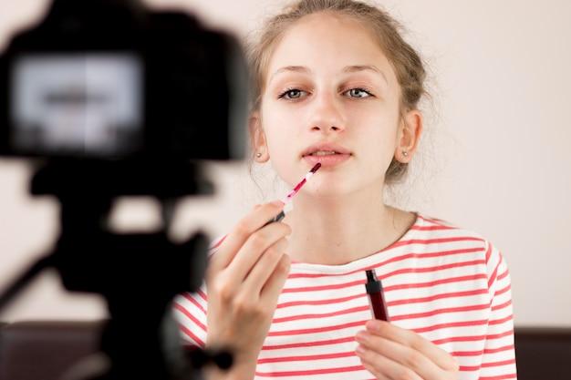 Medium shot blogger using lipstick Free Photo