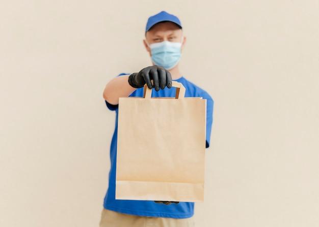 Uomo sfocato del colpo medio che tiene il sacchetto di carta Foto Gratuite