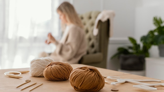 Donna sfocata del colpo medio che lavora a maglia all'interno Foto Gratuite