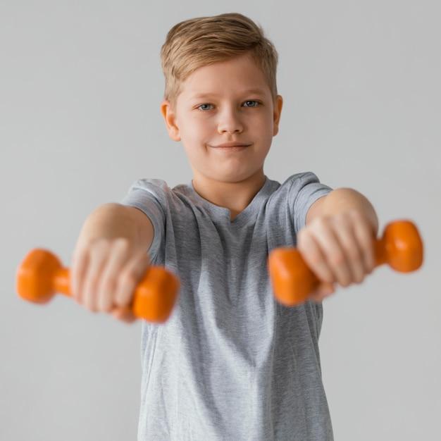 ダンベルを持っているミディアムショットの少年 無料写真