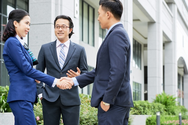 Medium shot of business people shaking hands outdoors Free Photo