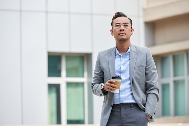 Medium shot of businessman holding the  takeaway coffee and looking forward standing in the street Free Photo