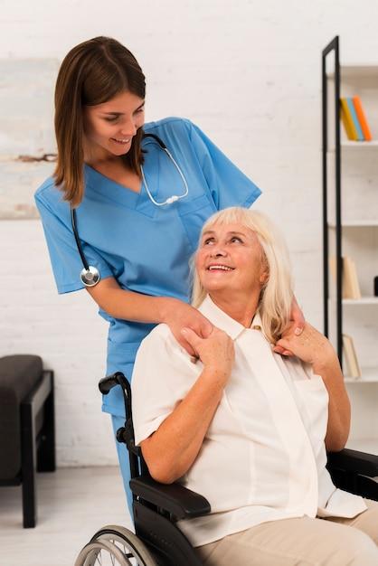 ミディアムショットの介護者とお互いを見て老woman Premium写真