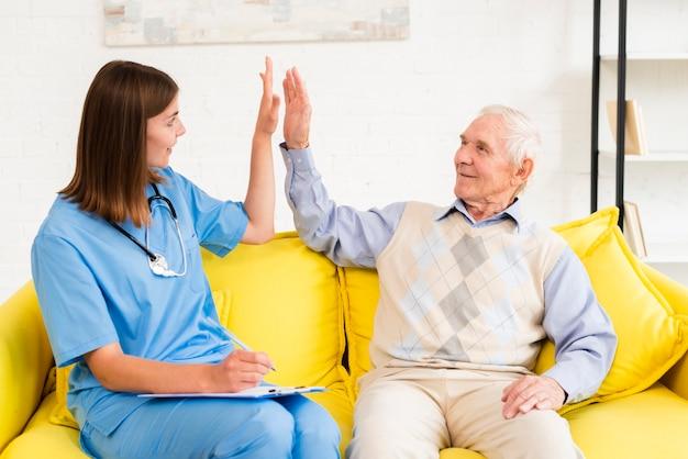 Medium shot caregiver high fiving with old man Free Photo