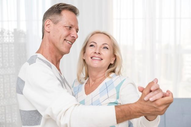 Средний снимок пара танцует в гостиной Бесплатные Фотографии
