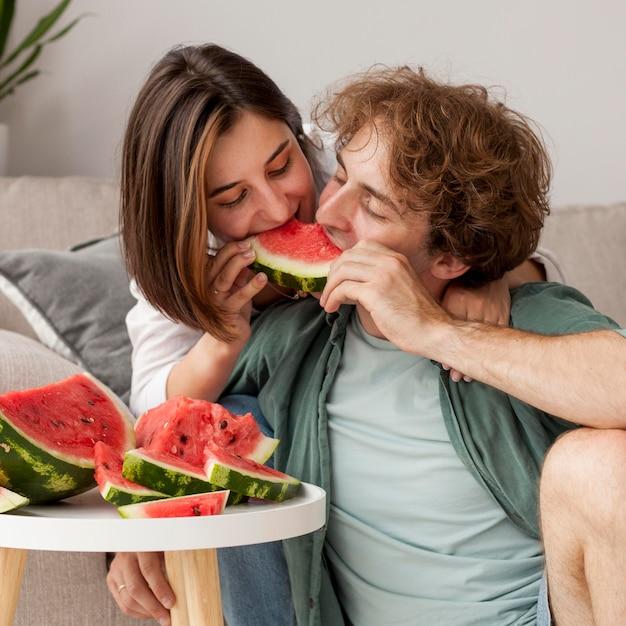 スイカを食べるミディアムショットのカップル 無料写真